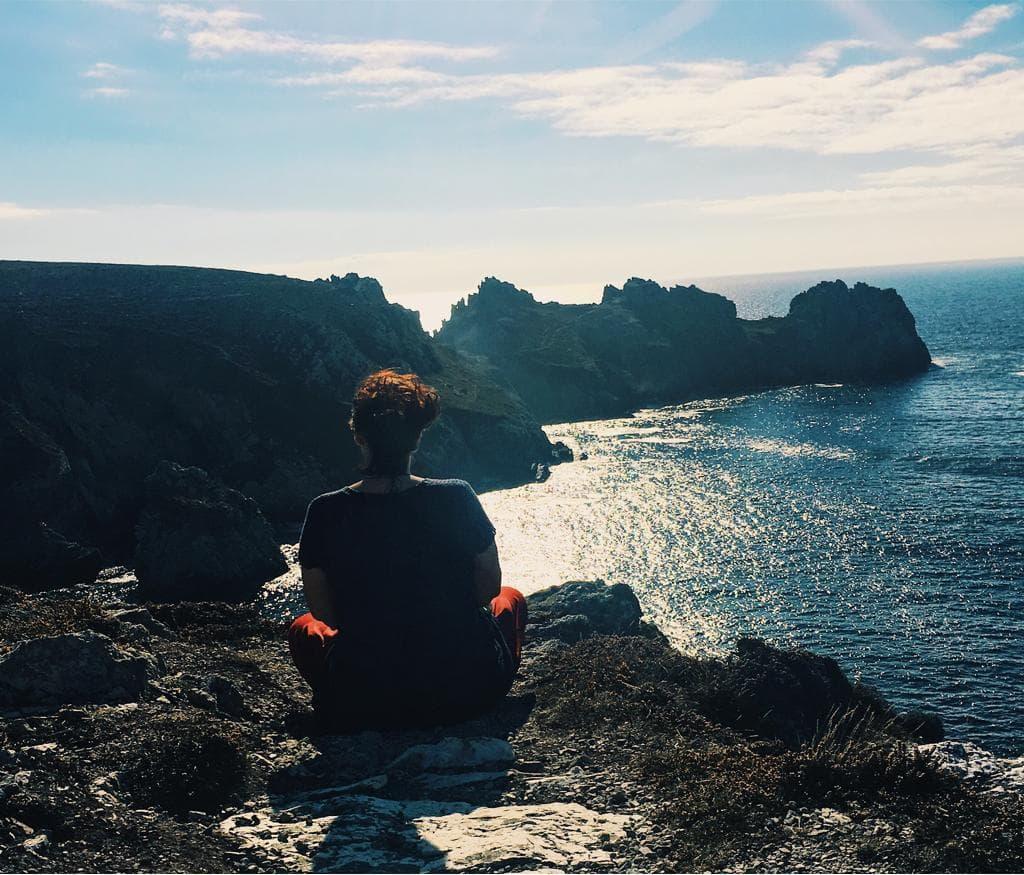 Frau sitzt auf einer Felsklippe in der Natur und meditiert